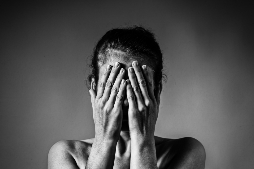 Concept of fear, shame, domestic violence. Woman covers her face her hands on light  scratched background. Black and white image.