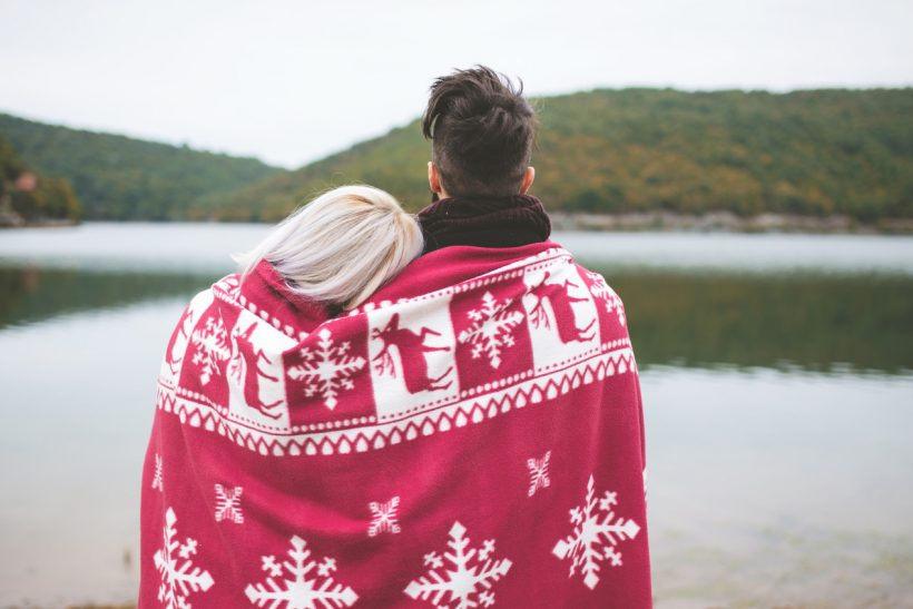 Back view of a couple hugging and watching beautiful lake