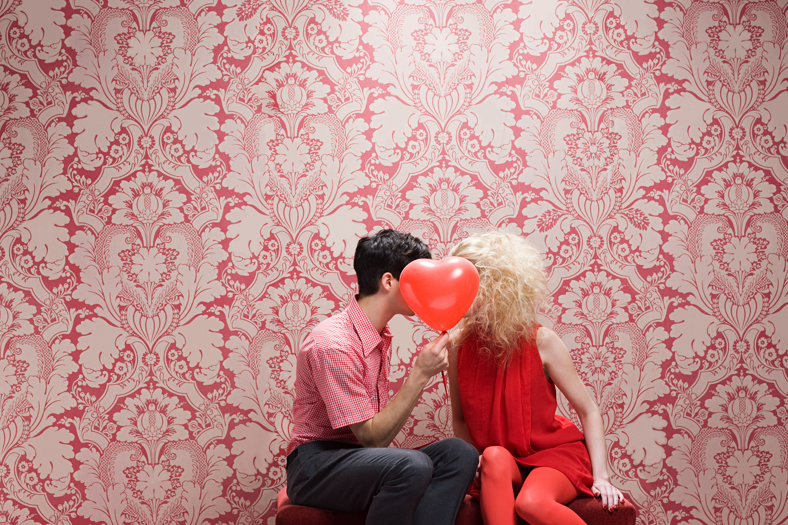 Couple behind heart shaped balloon