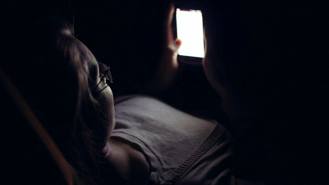 HC8WF2 Young woman using mobile phone in dark room at home