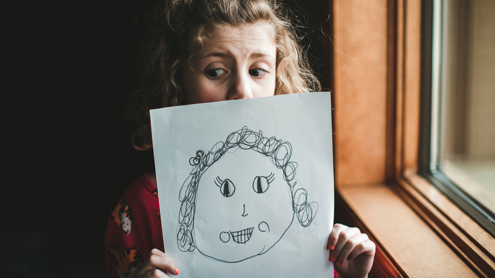 Little girl with curly hair holds up a self portrait that she drew of herself and peeks over it while standing indoors next to a window.