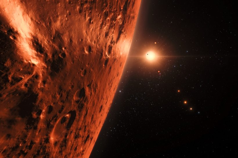 This artist's impression shows the view from the surface of one of the planets in the TRAPPIST-1 system. At least seven planets orbit this ultracool dwarf star 40 light-years from Earth and they are all roughly the same size as the Earth. Several of the planets are at the right distances from their star for liquid water to exist on the surfaces. This artist's impression is based on the known physical parameters of the planets and stars seen, and uses a vast database of objects in the Universe.